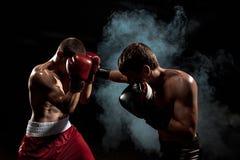 Boxareboxning för två professionell på svart rökig bakgrund, arkivbilder