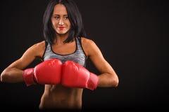 Boxarekvinna med röda boxninghandskar på Arkivbild