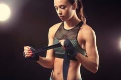 Boxarekvinna som applicerar handledsjalar Arkivbild