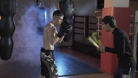 Boxaren fullgör slagen tillsammans med lagledaren En sportgrabb i boxninghandskar på boxning tafsar, arbeta som privatlärare åt e arkivfilmer