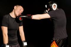 Boxaren som landar en stansmaskin på hans motståndare, snackar Royaltyfri Fotografi
