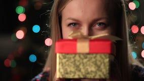 Boxas hållande julklapp för den lyckliga unga kvinnan arkivfilmer
