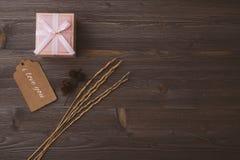 Boxas med en gåva på en trämörk bakgrund, med en inskrift, utrymme för text, bästa sikt royaltyfri foto