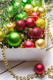 Boxas med röda, guld- och gröna julbollar vita röda stjärnor för abstrakt för bakgrundsjul mörk för garnering modell för design Arkivbild