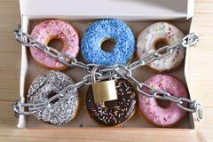 Boxas mycket av att fresta läckra donuts som slås in i metallkedja och, låsa i socker och söt böjelse Arkivbild