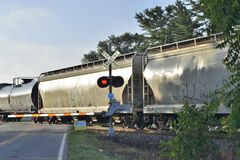 Boxcars and oil tanks at crossing Royalty Free Stock Image