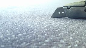 Boxcutter on grey carpet. Cutting carpet knife Stock Photo