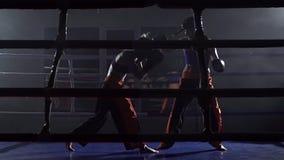 Boxe de treino no anel entre duas meninas em um espaço escuro Movimento lento filme