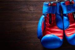 Boxe des gants bleus et rouges pendant des cordes sur un fond en bois images stock
