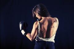 Boxe forte de jeune femme exécutant un coup-de-pied d'uppercut photo libre de droits