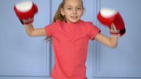 Boxeador alegre de la muchacha en los guantes de boxeo que saltan y que disfrutan la cámara lenta del triunfo almacen de video