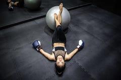 Boxeador asiático de la muchacha que miente con la bola del ejercicio en gimnasio fotos de archivo libres de regalías