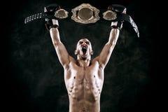 Boxeador con la correa de campeón que celebra la victoria sin defectos aislado en fondo negro con el espacio de la copia Imagenes de archivo