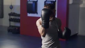 Boxeador con los guantes de boxeo que resuelve soplos en la c?mara en el gimnasio, lucha de la sombra, c?mara lenta metrajes