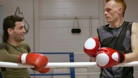 Boxeador de dos mangos en los guantes de boxeo que descansan sobre el anillo después del entrenamiento intensivo en club de la lu almacen de video
