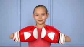 Boxeador de la chica joven del retrato en los guantes de boxeo listos a luchar en el cierre u del anillo almacen de metraje de vídeo