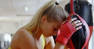 Boxeador de sexo femenino agotado mientras que boxeo en el estudio 4k de la aptitud almacen de metraje de vídeo