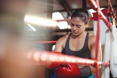 Boxeador de sexo femenino cansado que se sienta en el anillo Imagen de archivo libre de regalías