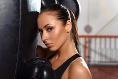 Boxeador de sexo femenino con el saco de arena Fotos de archivo