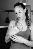 Boxeador de sexo femenino joven que ata encima de las manos fotografía de archivo