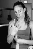 Boxeador de sexo femenino que ata encima de sus manos foto de archivo