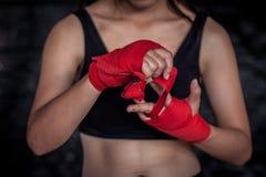 Boxeador de sexo femenino que envuelve la mano y el finger para la práctica Fotos de archivo libres de regalías