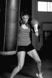 Boxeador de sexo femenino que golpea el bolso de perforación con el pie imagenes de archivo