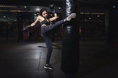 Boxeador de sexo femenino que golpea un saco de arena enorme en un estudio del boxeo Boxeador de la mujer que entrena difícilment imagen de archivo