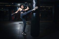 Boxeador de sexo femenino que golpea un saco de arena enorme en un estudio del boxeo Wom fotografía de archivo libre de regalías