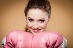 Boxeador de sexo femenino que lleva los guantes grandes del rosa de la diversión que juegan deportes Foto de archivo libre de regalías