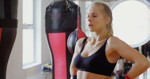 Boxeador de sexo femenino que se relaja en el estudio 4k de la aptitud metrajes