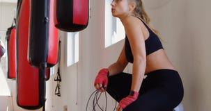 Boxeador de sexo femenino que se relaja en el estudio 4k de la aptitud almacen de metraje de vídeo