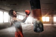 Boxeador de sexo masculino asiático potente con el saco de arena Fotos de archivo