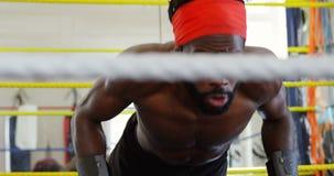 Boxeador de sexo masculino que ejercita en el ring de boxeo 4k almacen de metraje de vídeo