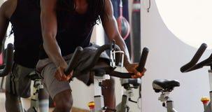 Boxeador de sexo masculino que ejercita en la bicicleta estática 4k almacen de metraje de vídeo