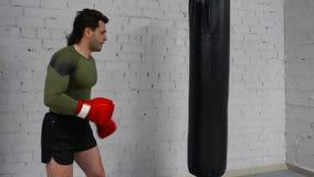 Boxeador del hombre en guantes que entrena para golpear el bolso del sacador con el pie almacen de video