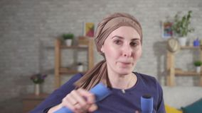 Boxeador fuerte joven de la mujer del retrato con el cáncer en una bufanda en su cabeza después de pesas de gimnasia involucradas metrajes