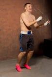 Boxeador joven apto que salta durante un entrenamiento Foto de archivo