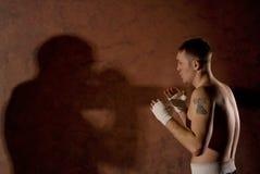 Boxeador joven que mira a su opositor en el anillo Fotos de archivo