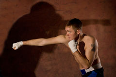 Boxeador joven que perfora a un opositor Foto de archivo libre de regalías