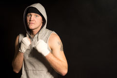 Boxeador joven resuelto serio en una sudadera con capucha Foto de archivo
