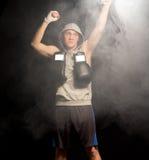 Boxeador joven serio que aumenta sus puños Fotografía de archivo