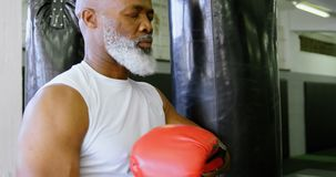 Boxeador mayor que se inclina contra el saco de arena 4k almacen de video