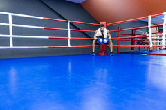 Boxeador que descansa en ring de boxeo Foto de archivo