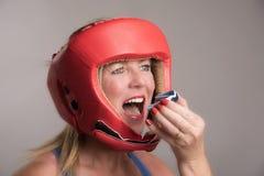 Boxeador que inserta un escudo de la goma en la boca Imágenes de archivo libres de regalías