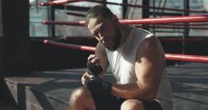 Boxeador que se sienta en el borde de un ring de boxeo profundamente en pensamiento después de para resolverse en gimnasio de nie almacen de video
