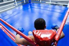 Boxeador que se sienta en la esquina del ring de boxeo Imagen de archivo