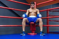 Boxeador que se sienta en ring de boxeo Fotos de archivo