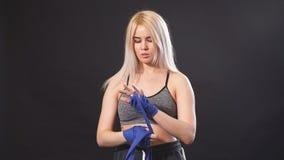 Boxeador rubio de sexo femenino que envuelve las manos con el vendaje elástico azul que se prepara al entrenamiento metrajes