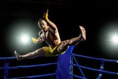 Boxeador tailandés en el ring de boxeo, el salto y el retroceso con el pie imagen de archivo